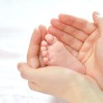 Ein Babyfuß in den Händen der Mutter - eine glückliche Familie