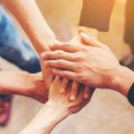 Teamworkkonzept - Hände zusammenlegen, um Einigkeit zu zeigen.